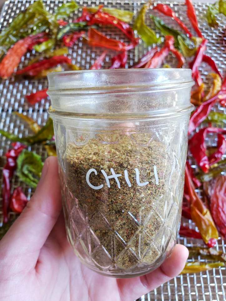 """DeannaCat's hand is in view holding a half pint mason jar that is two thirds full of ground chili powder. The word """"chili"""" has been written on the glass with a grey pen. The background is a stainless steel dehydrator rack full of dried chilis that are various shades of red and green."""