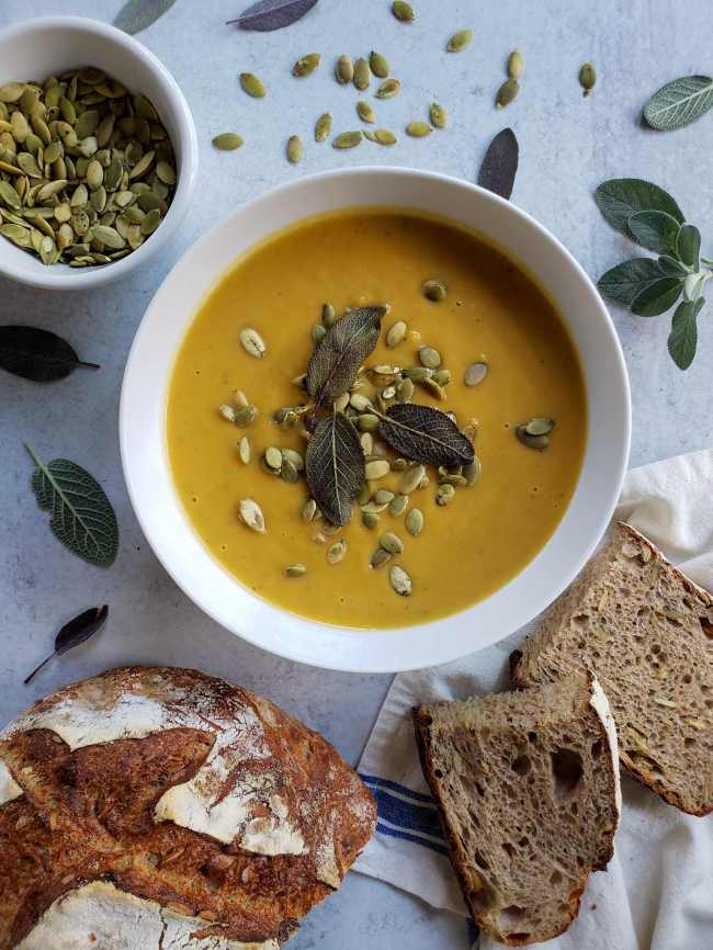 The finished butternut squash soup is the center of an image that is being taken on a washed concrete type surface. The white bowl sits in the center almost full of the soup, it has been garnished with a handful of sprouted pumpkin seeds and three fried sage leaves. There is a white ramekin just above the soup that is partly full of sprouted pumpkin seeds, green sage leaves are scattered evenly throughout the surface, while half a loaf of sourdough bread lays beneath it. Two slices of bread lay next to the loaf and bowl of soup, revealing a darker wheat bread with seeds mixed in as well.