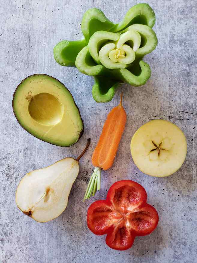 The produce is arranged in a cluster, centering around the carrot. Each of the produce items is now cut and only half of the fruit is shown. The avocado, carrot, and pear have been sliced in half lengthwise, while the bell pepper, apple and celery have been cut in half widthwise.