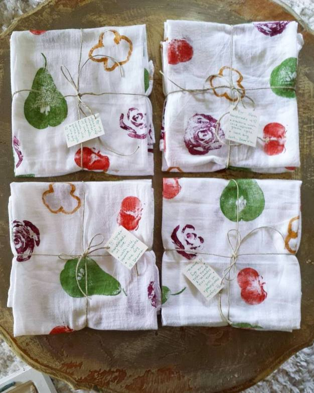 Four sets of of fruit and veggie stamped tea towels sit atop a table. Each set is folded into a square and it has a piece of twine wrapped around it as one would a present. Each one is adorned with a paper card that has been attached with the twine.