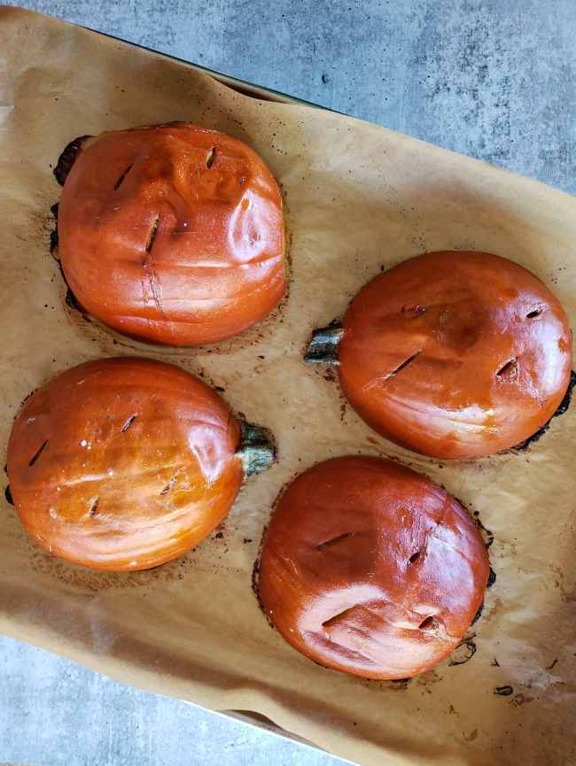 Four halves of sugar pie pumpkins are shown on a baking sheet after they have been roasted. They were placed flesh side down so only their skin is visible. The pumpkins have partially caramelized, as seen by the dark brown to black spots visible along their edges. Knife slits have been made in a few places along the skin of each pumpkin to help release steam.