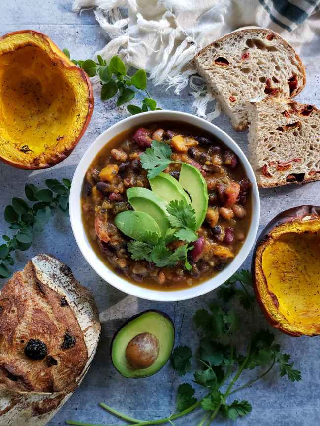 The roasted pumpkin chili is shown garnished with avocado slices and cilantro leaves. Surrounding the bowl in a decorative fashion are halves of roasted pumpkin, slices of sourdough bread as well as half of the remaining loaf, half an avocado, sprigs of cilantro, and sprigs of oregano.