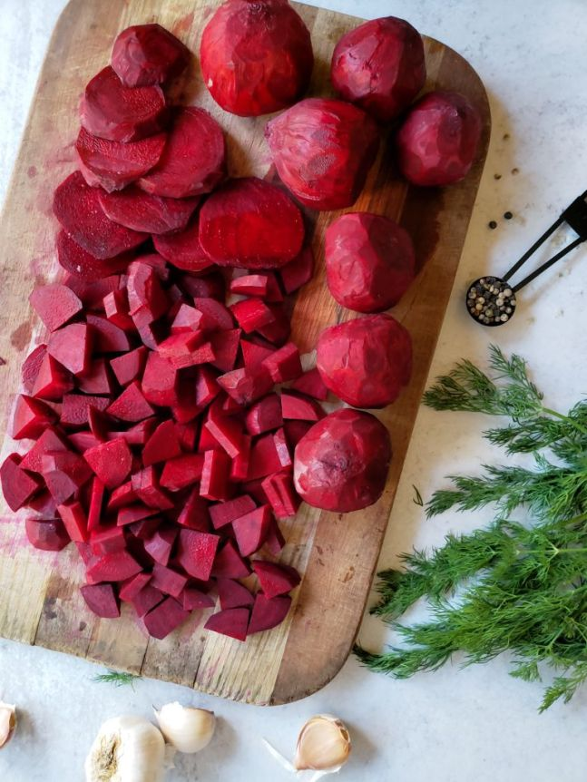 A wooden cutting board is covered in red beets, half of the board is taken up by bite sized chunks of beets while the other half contains whole beets that have been peeled. Next to the board lays a few sprigs of dill, a couple cloves of garlic, and a teaspoon measuring spoon full of multi colored peppercorns.