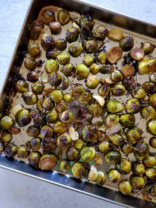 The marinated brussels sprouts are shown on the baking sheet after they have finished roasting in the oven. Portions of the brussels sprouts and garlic and crispy brown from the roasting.