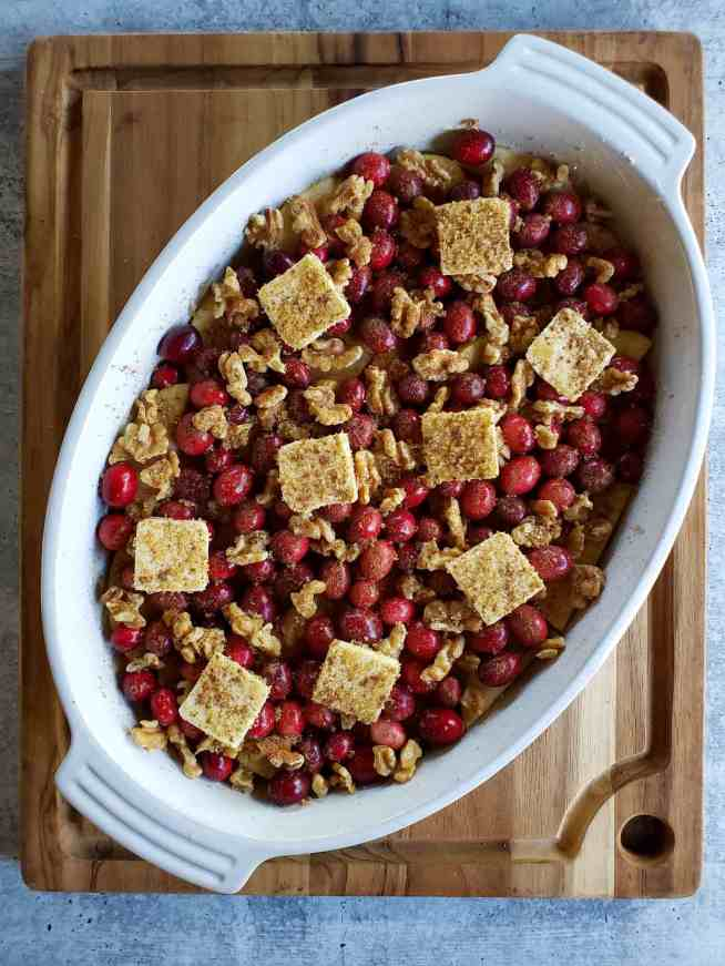 A white oval baking dish is shown after one layer each of the sweet potatoes, apples, cranberries, walnuts have be sprinkled with salt, brown sugar, cinnamon, allspice, and nutmeg while nine tabs of butter are evenly dispersed over the top as well.