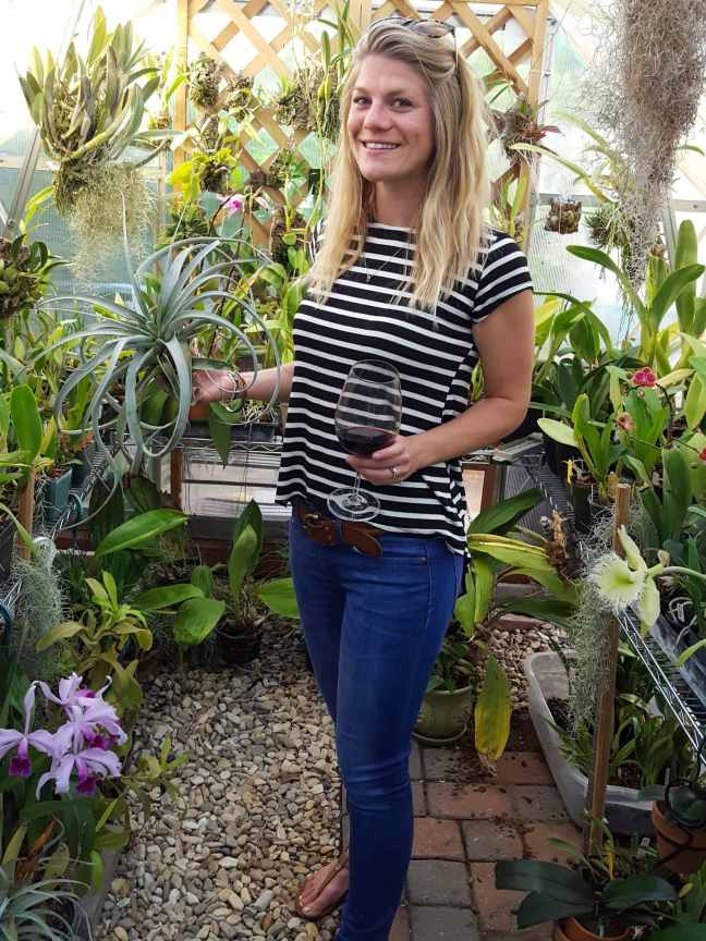 DeannaCat is standing inside a hobby greenhouse that is full or orchids, bromeliads, and tillandsia air plants. Some are flowering white, purple, or light pink. Some are perched on trellises and others are on shelving units. DeannaCat is holding a larger air plant in one hand and a glass of red wine in the other. She is wearing blue jeans and a striped white and black shirt.
