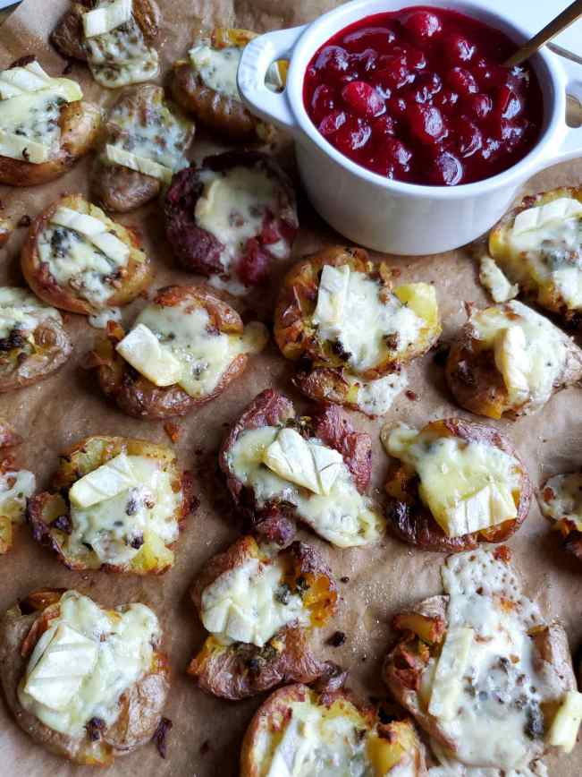 Two bite smashed potatoes are shown after they have been topped with a soft cheese and allowed to bake for the final few minutes. Each potato has turned a crispy brown and the cheese has melted, some of it oozing off the edges of the potato. The garlic and herb is still visible underneath the cheese. A white ramekin full of fresh cranberry sauce has been served alongside the potatoes. The sauce still  has plenty of whole cranberries that haven't fully broken down yet.
