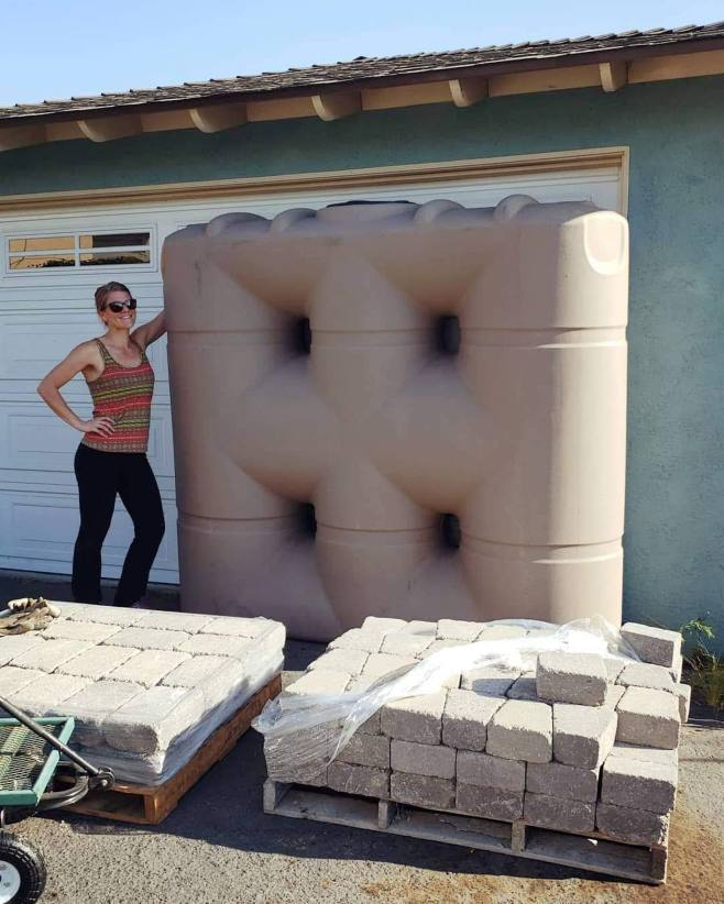 DeannaCat is standing next to the newly purchased 530 gallon slimline rain tank. This is a great tank for rainwater collection in narrow spaces. There are two pallets of pavers and stones sitting in front of them, though these are for a separate project unrelated to the rain water tank.