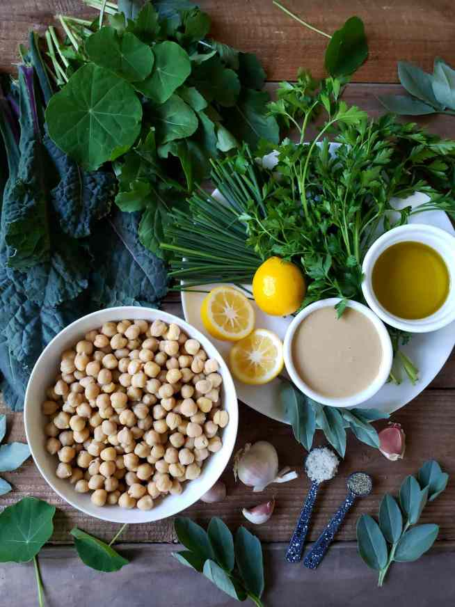 The ingredients used for making a green humus recipe are shown. A white ceramic bowl of garbanzo beans, a white ramekin of tahini, a white ramekin of olive oil take up the center of the image with chives, Italian parsley, garlic, salt, pepper, lemons. Lacinato kale, nasturtium leaves, and some Fava leaves are laid out around them.