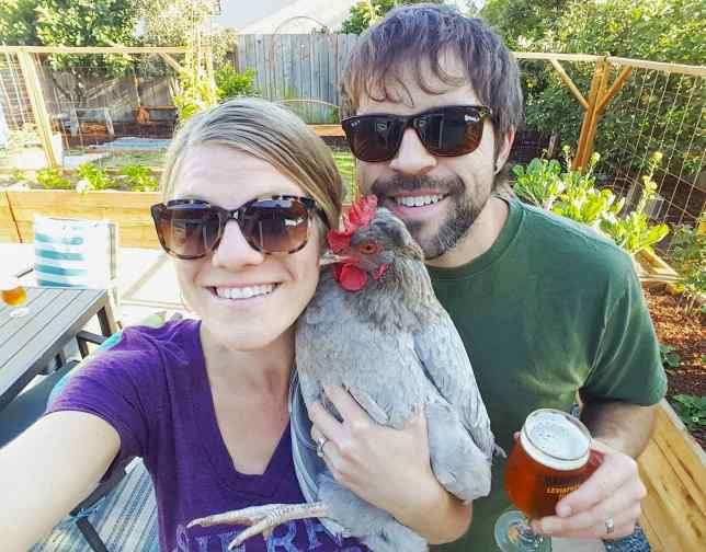 DeannaCat and Aaron standing in their newly designed and constructed patio garden. DeannaCat is holding a grey chicken and Aaron is holding a glass of beer. Vegetable plants have been planted and can be seen in the new garden beds.
