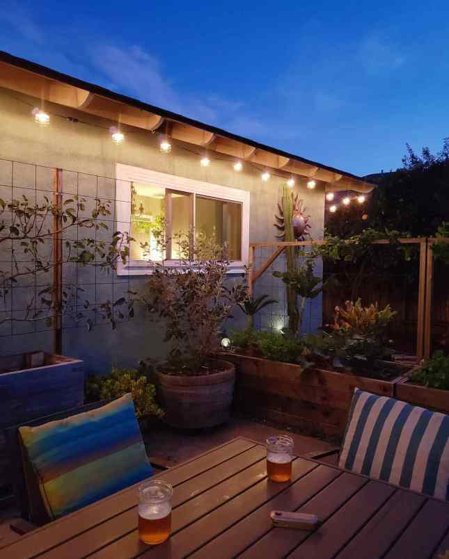 The backyard patio is shown during dusk. There are two beers on the patio table and the string lights that line the eaves of the house are lit. When one starts a homestead, it is a good idea to take time for yourself and relax on occasion.