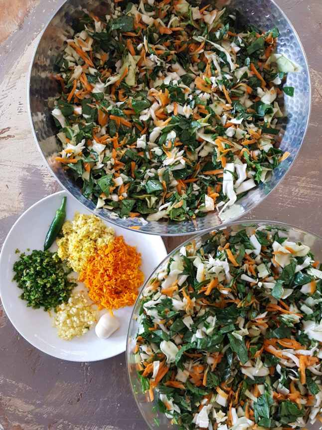 Two bowls of various chopped greens and grated carrot are shown. There is a small white plate next to the bowls that contains the seasonings for the kraut. Chopped fresh turmeric, chopped fresh ginger, chopped fresh garlic, and chopped fresh chili peppers are taking up their portion of space on the plate.
