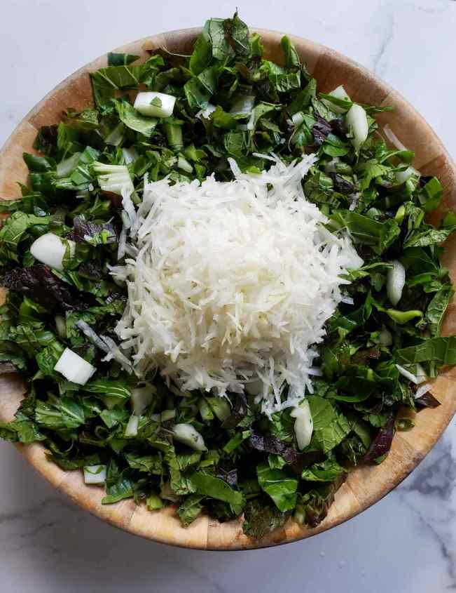 A large wooden bowl is shown full of chopped bok choy and red mustard greens. A pile of grated daikon radish is sitting in the middle of the chopped greens.