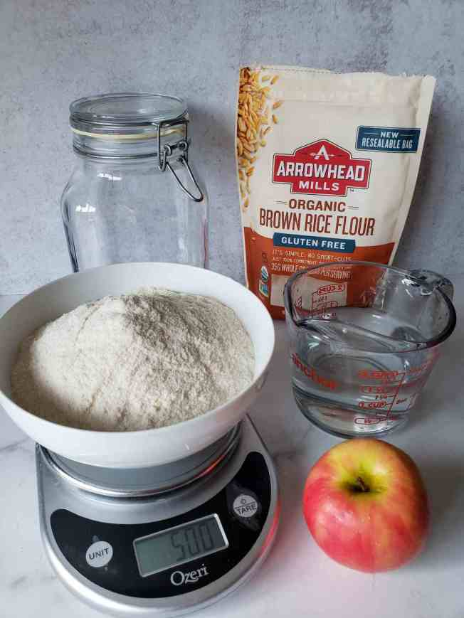 An image showing a white bowl of flour sitting on top of a kitchen scale that is registering 500 grams in weight. Next  to the bowl and scale is an apple and behind the apple is a glass measuring cup that has 1.5 cups of water in it. In the very back there is a bag of Arrowhead Mills Organic Brown Rice Flour and an empty two liter jar with a snap on lid. These are the ingredients to make your own gluten-free sourdough starter.