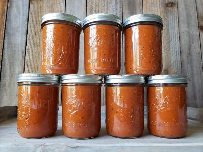 Seven pint jars of roasted tomato sauce are shown, four jars along the bottom with three jars stacked on top of the bottom four. The sauce is dark red in color with specks of black from the roasting. When you grow tomatoes, preserving them is a must to make the most of your harvest.