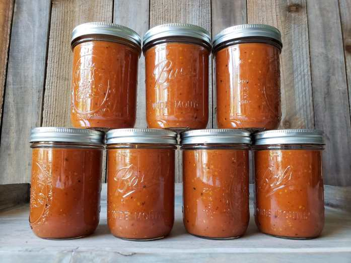 Seven pint sized mason jars lined up with four on the bottom and three sitting on the top, placed off center to the ones below. The jars of full of simple tomato sauce.