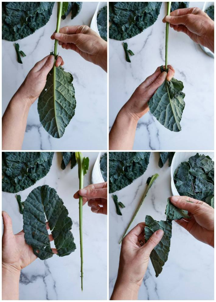 A four way image collage on how to de-stem kale. The first image shows a hand holding a piece if kale by the stem, the second hand is pinching the kale stem where the greens are attached. The second image shows a hand holding the isle stem while the second hand is pulling the kale leaf by sliding g it along the stem which tears the leaf portion from the stem. The third image shows one hand holding the lone leftover stem while the other hand is holdingthe hdetached kale leaf. The fourth image shows two hands illustrating a chunk of the leaf that will be torn into a kale chip size portion. Below shows a strainer of de-stemmed kale torn into chip size pieces and a bunch of kale that still needs to be prepped.