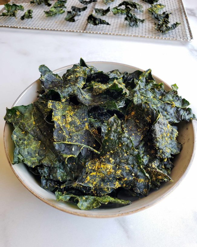 A bowl of seasoned kale chips are shown with a stainless steel drying rack  with more finished chips shown in the background.