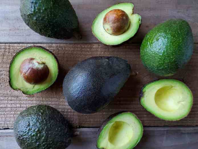A number of whole and halved avocados are arranged on a wooden board. They each are at a varying stage of ripeness, some green, some dark green, while a large ripe avocado that is black in color sits in the middle. The avocados that have been cut in half reveal their creamy green fruit within.