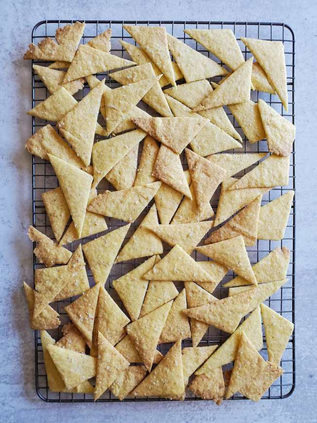 A wire cooling rack is full of freshly baked sourdough corn chips. Most are in a triangular shape aside from the odd ends and pieces. The rack isn't quite big enough for all the chips so they are overlapping and stacked on top of each other in some sections. The chips are a nice golden to golden brown in color.