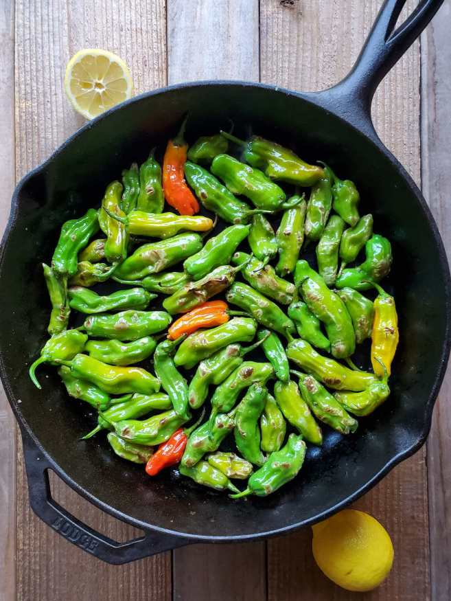 A birds eye view of a cast iron skillet full of partially blistered shishito peppers. Parts of the peppers have raised brown charred marks on them while the majority of the peppers are still vibrant green.