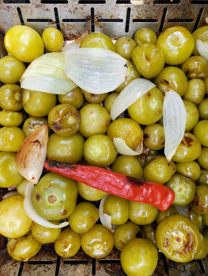 A close up image of a grilling basket full of the tomatillos, onion, garlic, and chili pepper after they have been roasted. Some of each of the ingredients are charred with brown exteriors.