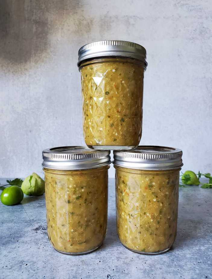 Three half pint mason jars with metal lids of green salsa are featured. There is one jar stacked on top of the middle of the two jars remaining below it. Fresh tomatillos and sprigs of cilantro are seen in the background.