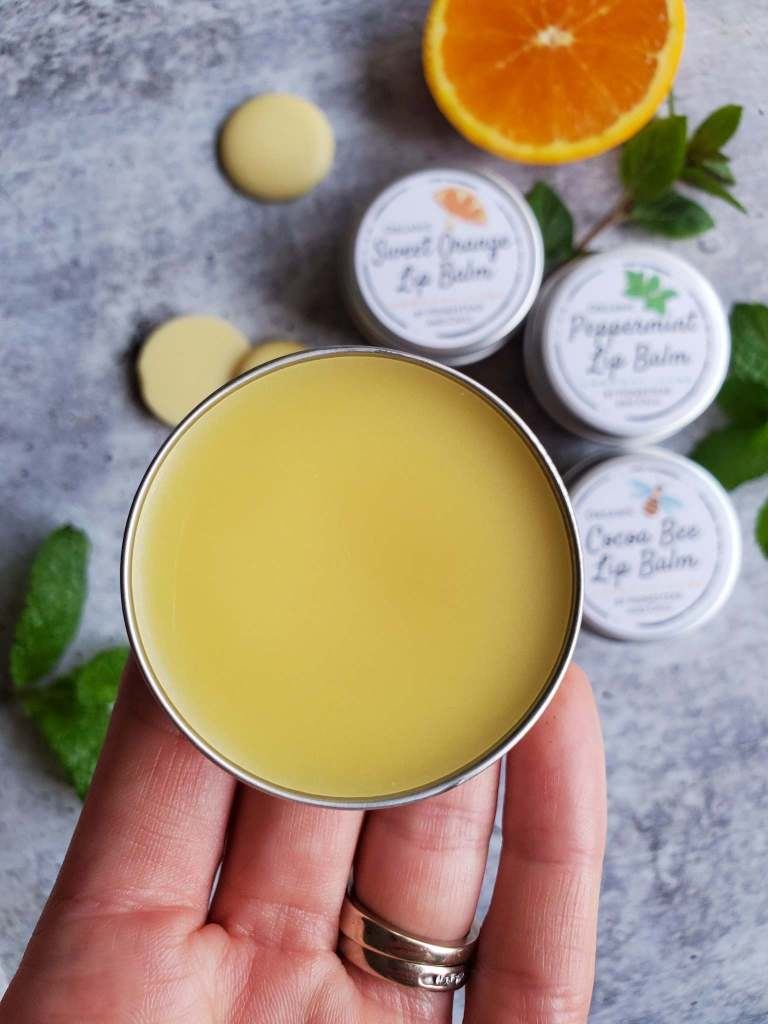 DeannaCat is holding a tin of homemade lip balm, the lid is off showing the beautiful light yellow balm inside. Below in the background lies another three lip balms with their lids and labels affixed on the tins. They are surrounded by cocoa butter pastilles, mint leaves, and half an orange.