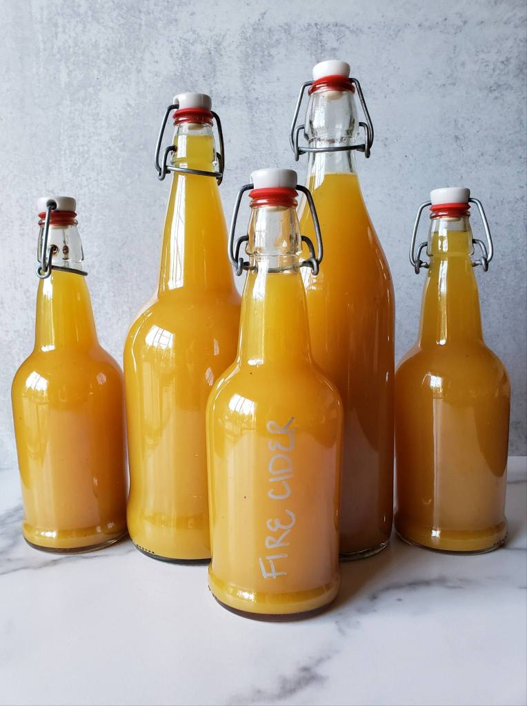 Five glass swing-top bottles of various sizes and shapes full of bright orange liquid, the finished strained homemade fire cider.