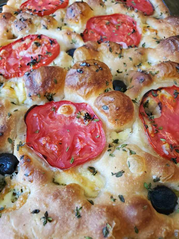 A close up image of a sourdough focaccia loaf that contains slices of tomato, black olives, slivered garlic, and fresh thyme. The top of the bread is bubbly with air, the bubbles are darker brown in color. Make sourdough healthier with active and bubbly sourdough starter.