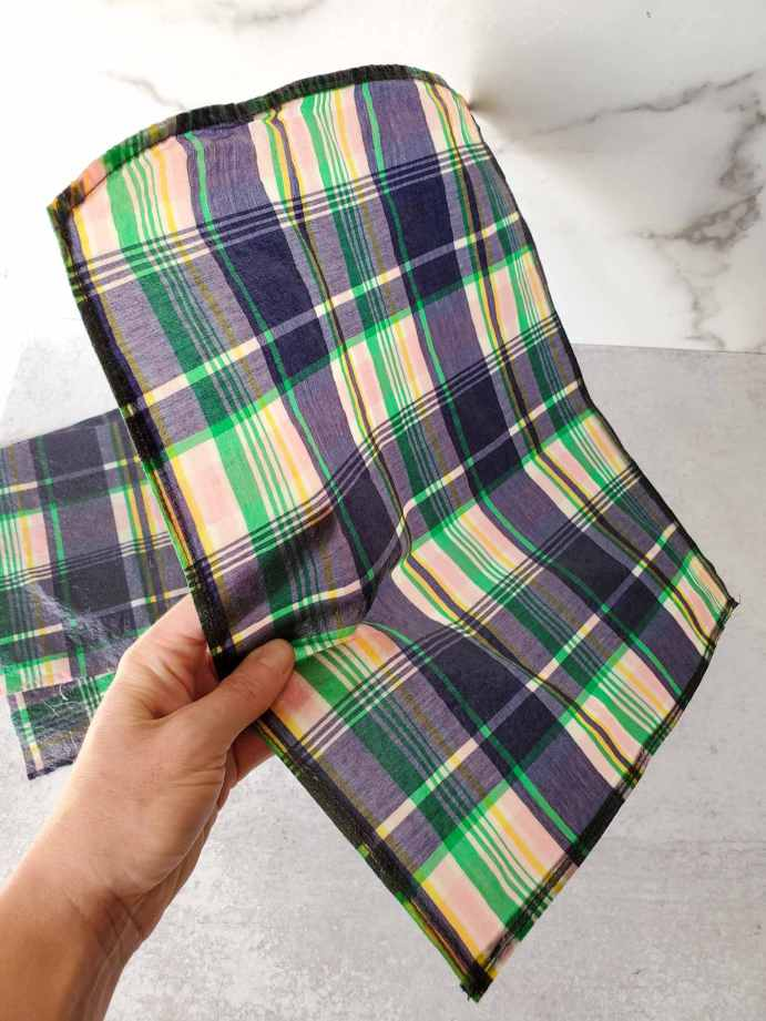 DeannaCat is holding a finished wrap to illustrate its stiffness though they are pliable when melded to cover food or containers. There is another beeswax wrap in the background, both are made from a 100% cotton blue and pink plaid shirt.