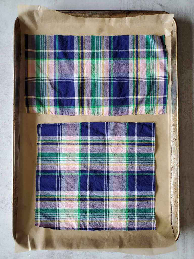 Two pieces of plaid cotton fabric are laid out on a baking sheet lined with parchment paper.
