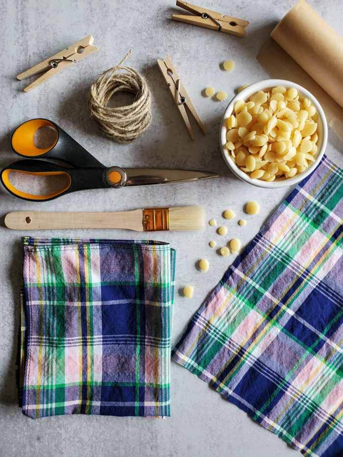 All the supplies needed to make homemade beeswax wraps are displayed. A small bowl of beeswax pastilles, shears, parchment paper, clothespins, twine, paint brush, and two pieces of 100% cotton fabric.