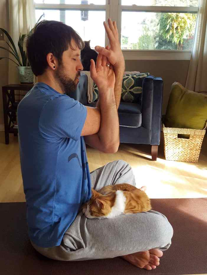 Aaron is sitting cross legged on a yoga mat with Quincey (an orange and white cat) on his lap. His arms are crossed in front of his body in an Eagle Arms pose. Beyond lies a chair and a window into the front yard.