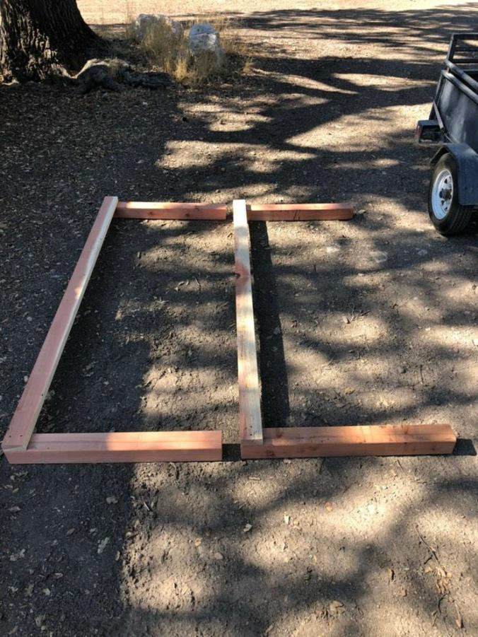 Two sides of a greenhouse bench are laying on the ground. Each side has two 4x4's which are connected together at the top by a long 2x4 board.
