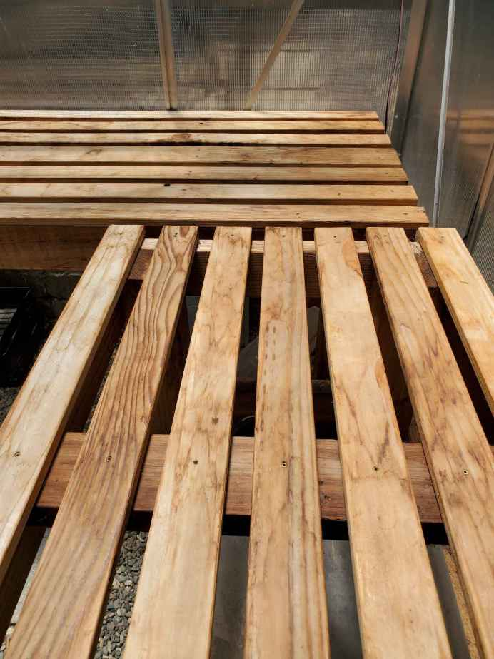 A close up image of the top of one of the greenhouse benches. The finishing screws are only slightly visible on the top of the bench. Build a greenhouse bench to maximize your space inside.