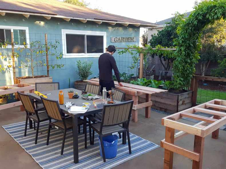 Aaron is standing over a greenhouse bench as it is being constructed. There are three benches throughout the patio, all of them in the same stage of construction, the only remaining step is to attach the top finishing planks. The patio table is littered with canteens of water, electric drill, screws, work gloves, and a notepad of the design.