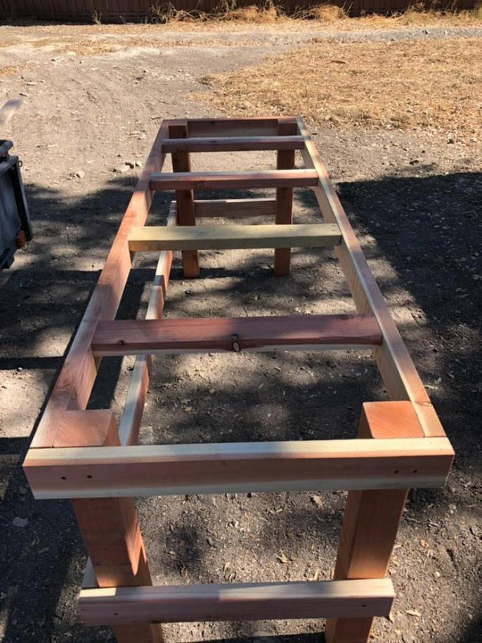The large greenhouse bench is almost fully constructed, its frame and table top supports are installed with only the finishing planks left to attach on the top.