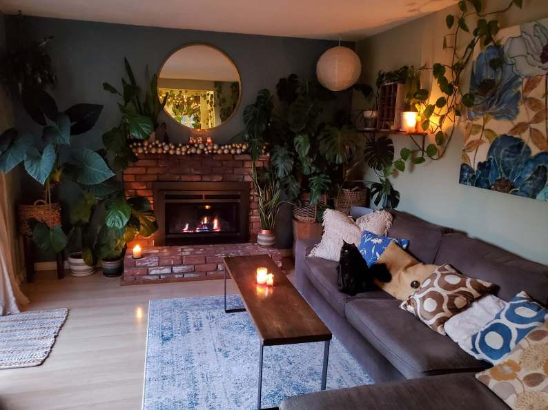A room is shown with a lit brick fireplace as the feature. A grey couch lines a wall with a black cat sitting on one of the cushions. There are candles lit throughout the room with two on the skinny, dark walnut coffee table, one on the fireplace, a few votives on the mantel, and one on a shelf above the couch. Various house plants of differing sizes dot the perimeter of the room.
