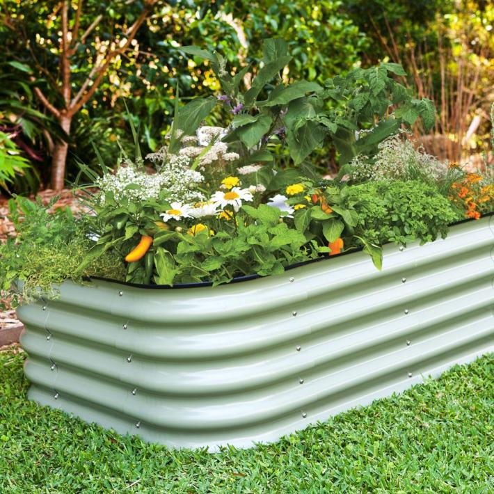 A long rectangular corrugated galvanized metal raised garden bed is sitting on grass. There are various flowers, herbs, perennials, and pepper plants planted amongst the bed.