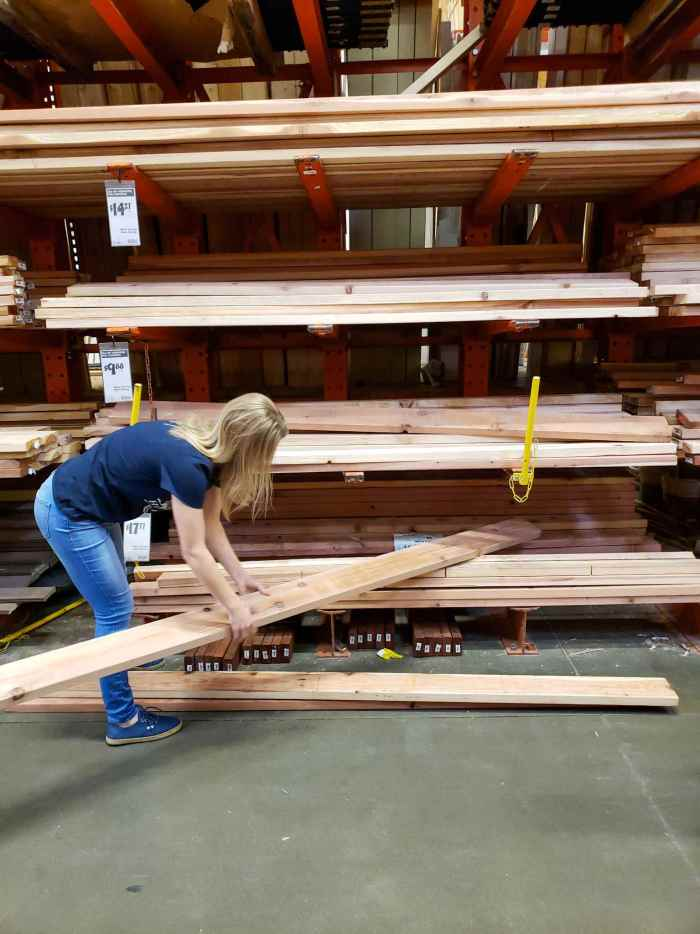 DeannaCat is grabbing a redwood 2x6 board for inspection from a shelf full of boards. There are multiple shelfs with varying sizes and wood materials that spans a height of at least 8 feet.