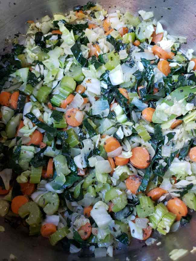 Celery, carrots, onion, kale, and cabbage are cooking inside a stock pot amongst a melange of chopped garlic, fresh herbs, and dried herbs. The next step is to add the broth to make your no-chicken noodle soup.