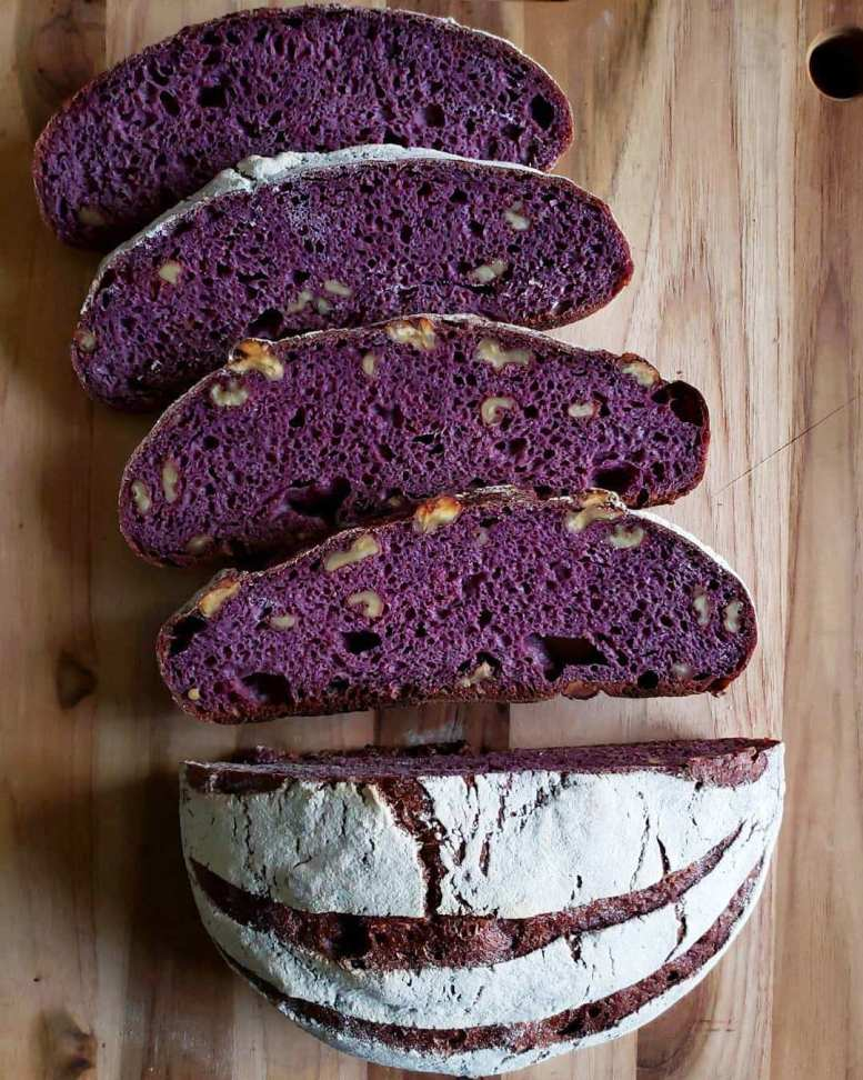 A sourdough boule loaf has been cut in half on a wood cutting board. One half of the loaf has been cut into four slices revealing a beautifully stark purple color inside with pockets of walnuts. The bread has been dyed with black nebula carrots which turned the entire loaf dark purple. The other half of the loaf has streaks of purple in the top from where the loaf was scored set against a floury white crust.