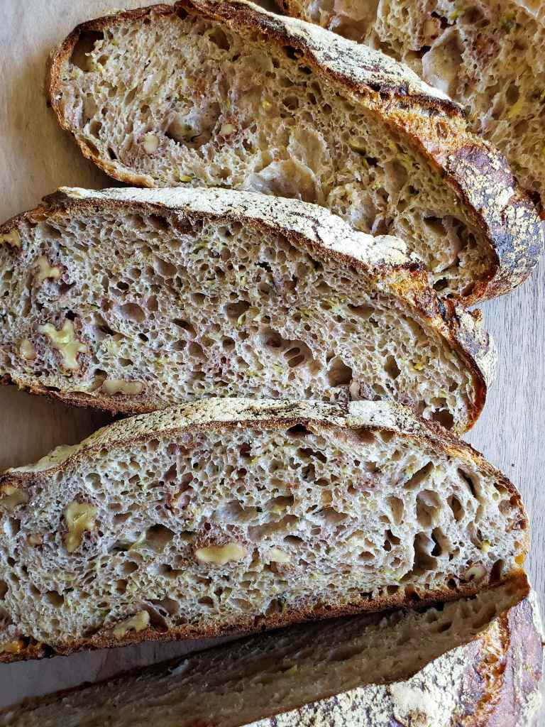 An image of 3 slices of sourdough bread displayed showing their insides. Below the slices there is the rest of the loaf of bread. There is a nice and brown crusty crumb showing on both sides of the bread and it is also littered with air holes, walnuts, and specks of zucchini.