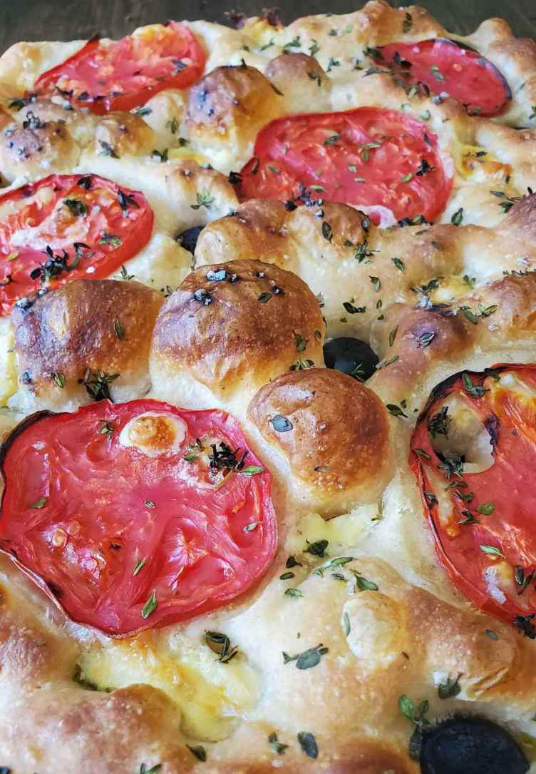 A close up of baked sourdough focaccia, with a light brown bubbly surface, flecks of little green thyme leaves, slices of round tomatoes, and black olives pressed into the dimples on top of the dough.