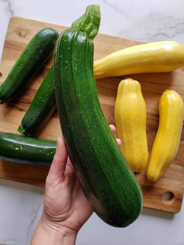 DeannaCat's hand is in view holding the featured large green zucchini. Below lies a wooden cutting board with three large yellow squash on one side and three large green zucchini on the other. Freeze zucchini when you have an abundance to save for later.