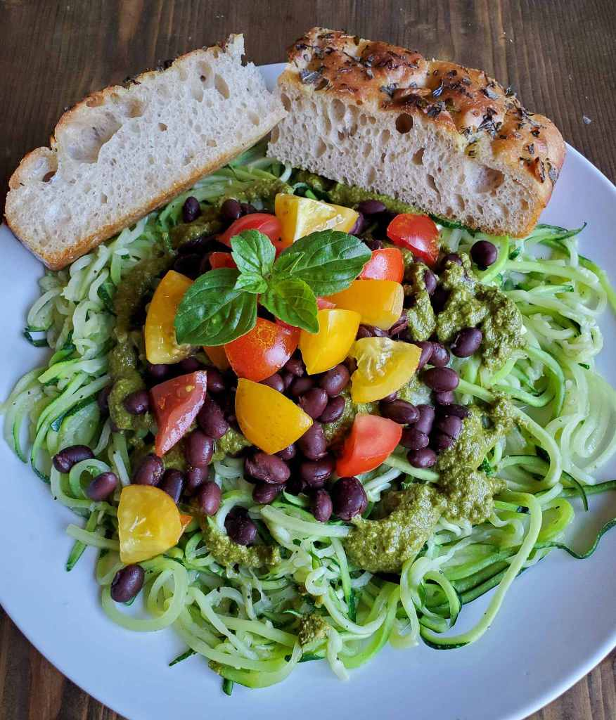 A white ceramic plate filled to the edges with cooked zucchini noodles topped with fresh pesto, black beans, red and yellow tomatoes and a garnish of basil with two slices of focaccia nestled against the edges of the noodles. When you have too much zucchini to use fresh, remember to freeze zucchini as well.