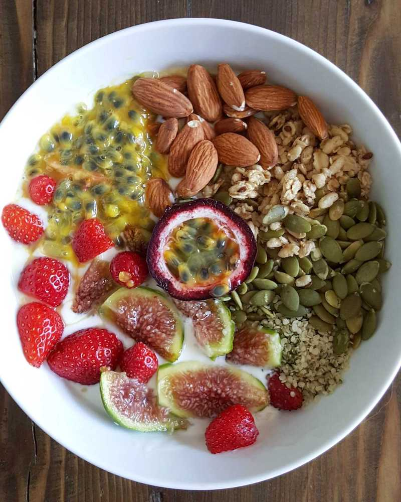 A white ceramic bowl which has ingredients spaced throughout the bottom like a pie cut into eight slices. There are hemp seeds, pumpkin seeds, granola, almonds, passionfruit pulp, strawberries, and cut figs rounding out the breakfast bowl.
