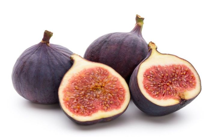 Dark purple to black skinned figs sit behind a fig that has been cut in half revealing a dark strawberry flesh. Choose fig varieties that are of interest to you and will do well in your zone.