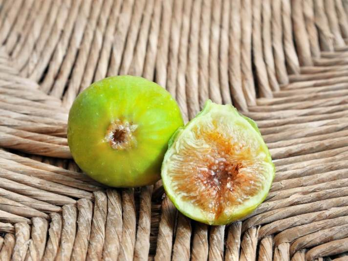 """Two green figs sit atop a wicker background. One of the figs has its """"eye"""" pointing straight ahead while the other fig has been cut in half to reveal its honey amber flesh. Choose fig varieties that have a closed """"eye"""" if you have wet growing conditions to reduce spoilage."""